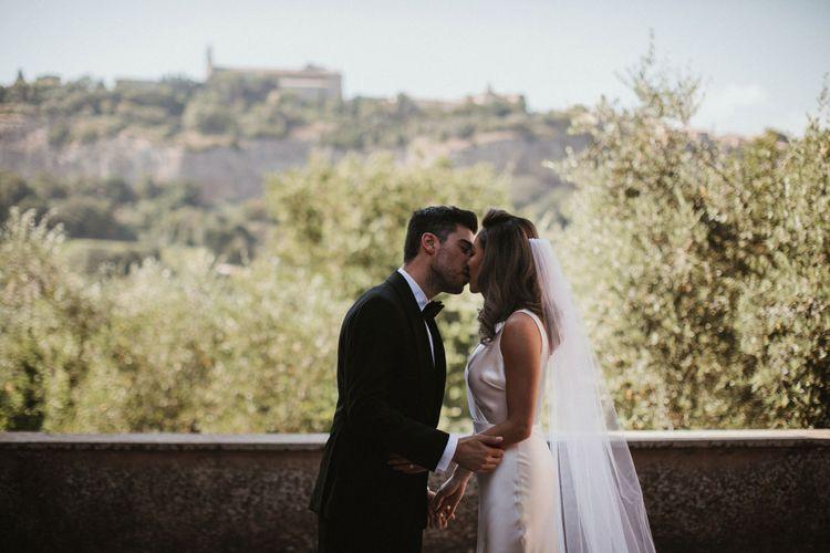 First Kiss   Bride in Silk Pallas Couture Wedding Dress with Plunging Neckline and Side Split   Roman & French Cathedral Veil   Groom in Made to Measure Tuxedo Suit by Oscar Hunt   Intimate Italian Castle Wedding with Prosecco Tower   James Frost Photography