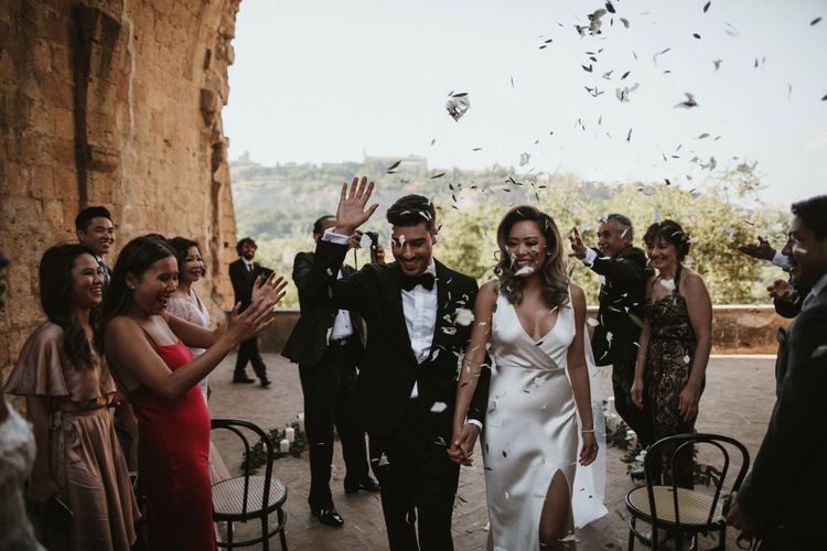 Confetti Throw   Newlyweds   Bride in Silk Pallas Couture Wedding Dress with Plunging Neckline and Side Split   Groom in Made to Measure Tuxedo Suit by Oscar Hunt   Intimate Italian Castle Wedding with Prosecco Tower   James Frost Photography