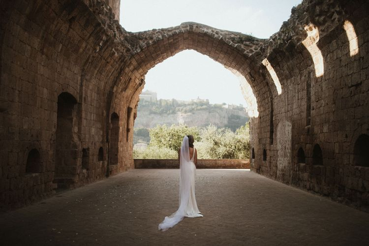 Bride in Silk Pallas Couture Wedding Dress with Plunging Neckline and Side Split   Roman & French Cathedral Veil   Intimate Italian Castle Wedding with Prosecco Tower   James Frost Photography