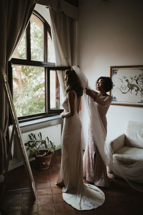 Bride Getting Into Her Gown   Silk Pallas Couture Wedding Dress with Plunging Neckline and Side Split   Roman & French Cathedral Veil   Mother of the Bride in Blush Pink Lace Dress   Intimate Italian Castle Wedding with Prosecco Tower   James Frost Photography