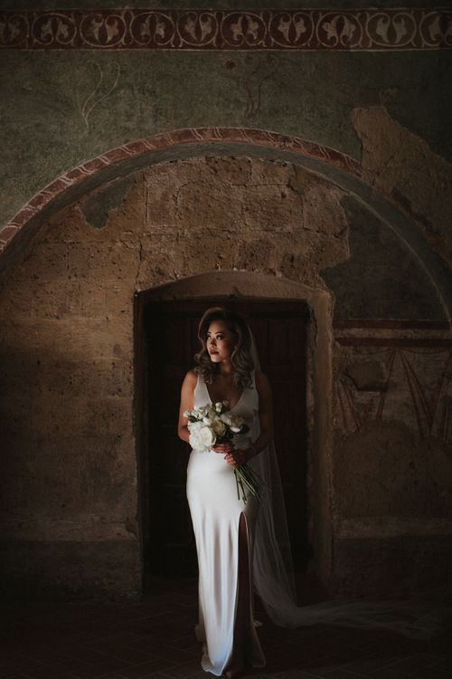 Bride in Silk Pallas Couture Wedding Dress with Plunging Neckline and Side Split   Roman & French Cathedral Veil   Long Stemmed Bridal Bouquet of White Flowers   Intimate Italian Castle Wedding with Prosecco Tower   James Frost Photography