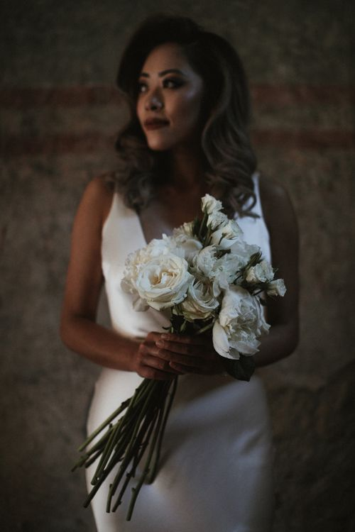 Bride in Silk Pallas Couture Wedding Dress with Plunging Neckline and Side Split   Long Stemmed Bridal Bouquet of White Flowers   Intimate Italian Castle Wedding with Prosecco Tower   James Frost Photography