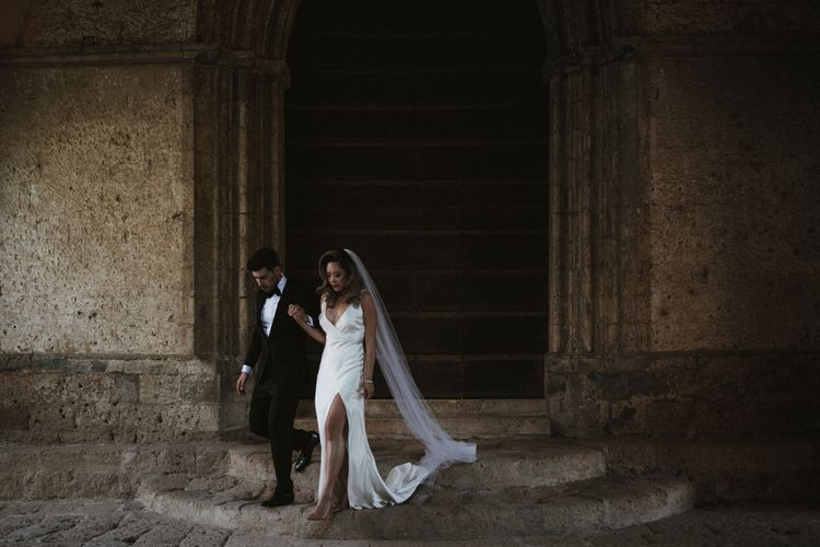 Bride in Silk Pallas Couture Wedding Dress with Plunging Neckline and Side Split   Roman & French Cathedral Veil   Salvatore Ferragamo Nude Bridal Shoes   Groom in Made to Measure Tuxedo Suit by Oscar Hunt   Black Aquila Shoes   Intimate Italian Castle Wedding with Prosecco Tower   James Frost Photography