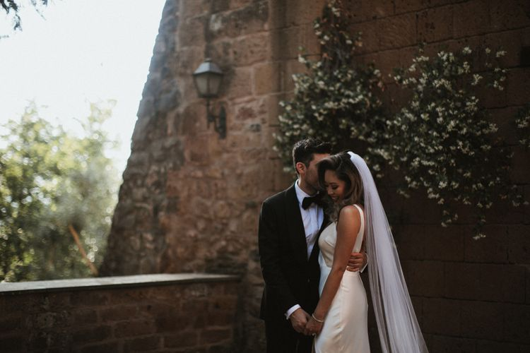Bride in Silk Pallas Couture Wedding Dress with Plunging Neckline and Side Split   Roman & French Cathedral Veil   Groom in Made to Measure Tuxedo Suit by Oscar Hunt   Intimate Italian Castle Wedding with Prosecco Tower   James Frost Photography