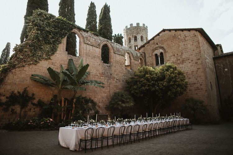 Wedding Breakfast Table in Courtyard at La Badia Di Orvieto Italy   White Tapered Candles   Hurricane Vases with White Flowers and Foliage   Intimate Italian Castle Wedding with Prosecco Tower   James Frost Photography