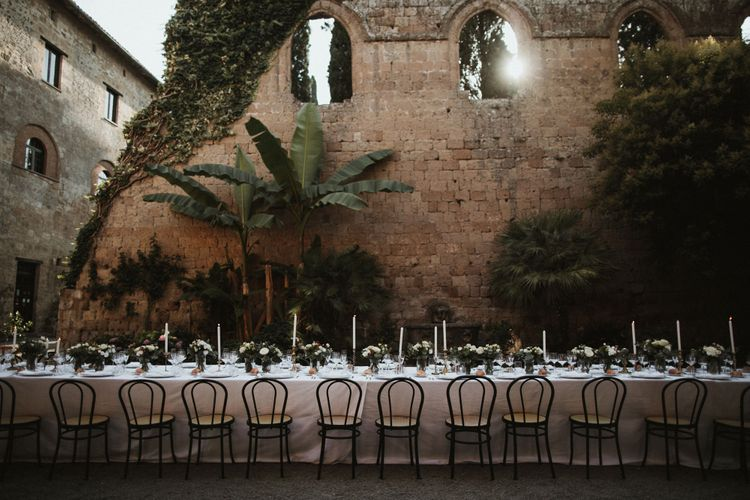 Wedding Breakfast Table in Courtyard at La Badia Di Orvieto Italy   White Tapered Candles   Gold Candlesticks   Hurricane Vases with White Flowers and Foliage   Intimate Italian Castle Wedding with Prosecco Tower   James Frost Photography