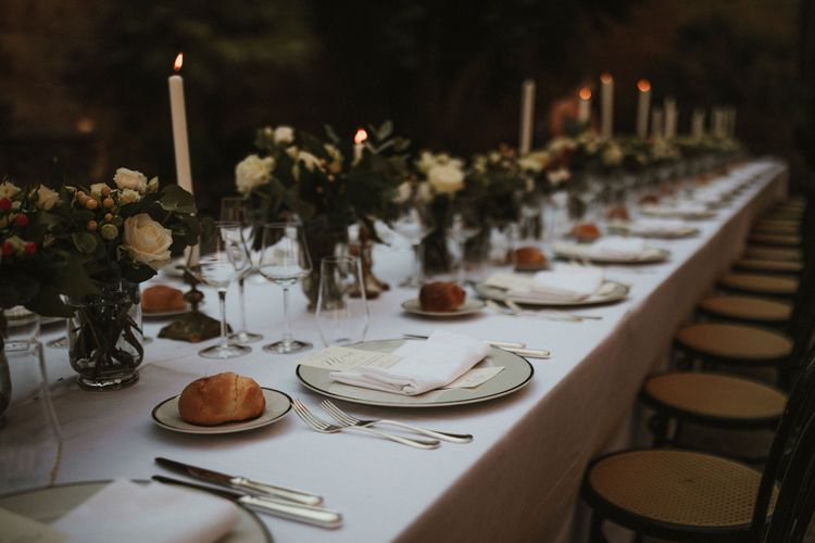 Wedding Breakfast Table in Courtyard at La Badia Di Orvieto Italy   White Tapered Candles   Gold Candlesticks   Hurricane Vases with White Flowers and Foliage   White Charger Plate with Gold Rim   Personalised Calligraphy Menu   Intimate Italian Castle Wedding with Prosecco Tower   James Frost Photography
