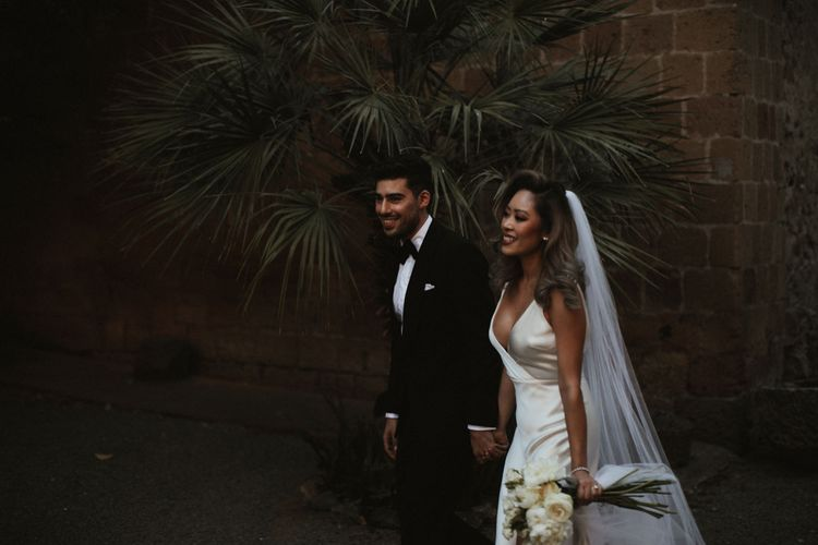 Bride in Silk Pallas Couture Wedding Dress with Plunging Neckline and Side Split   Roman & French Cathedral Veil   Long Stemmed Bridal Bouquet of White Flowers   Groom in Made to Measure Tuxedo Suit by Oscar Hunt   Intimate Italian Castle Wedding with Prosecco Tower   James Frost Photography