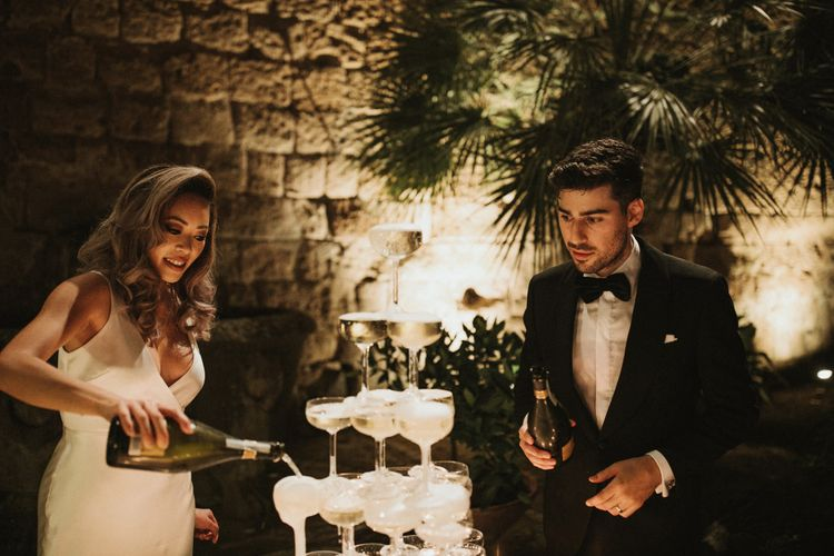 Prosecco Tower   Coupe Glasses   Bride in Silk Pallas Couture Wedding Dress with Plunging Neckline and Side Split   Groom in Made to Measure Tuxedo Suit by Oscar Hunt   Intimate Italian Castle Wedding with Prosecco Tower   James Frost Photography