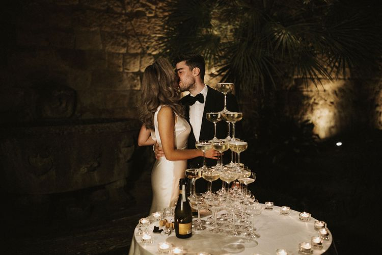 Prosecco Tower   Coupe Glasses   Tea Lights   Bride in Silk Pallas Couture Wedding Dress with Plunging Neckline and Side Split   Groom in Made to Measure Tuxedo Suit by Oscar Hunt   Intimate Italian Castle Wedding with Prosecco Tower   James Frost Photography