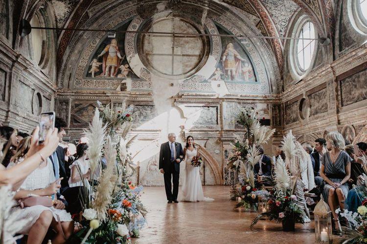 Stunning wedding ceremony with bright wedding flowers and pampas grass decor