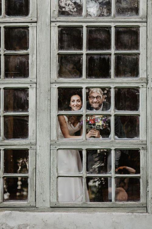 Brid and groom look out at guests at Italian villa