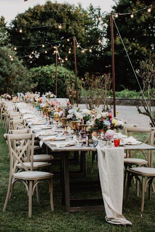 Bright flower centrepieces at outdoor wedding breakfast