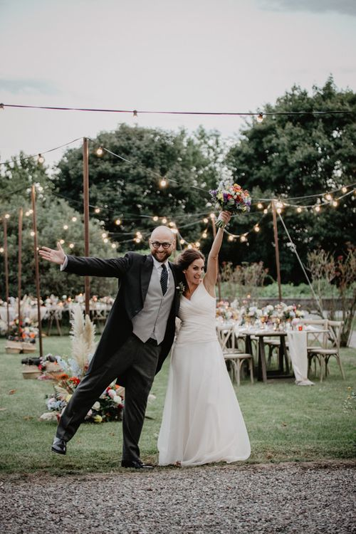 Festoon lighting over wedding breakfast tables with bright flower centrepieces and candles