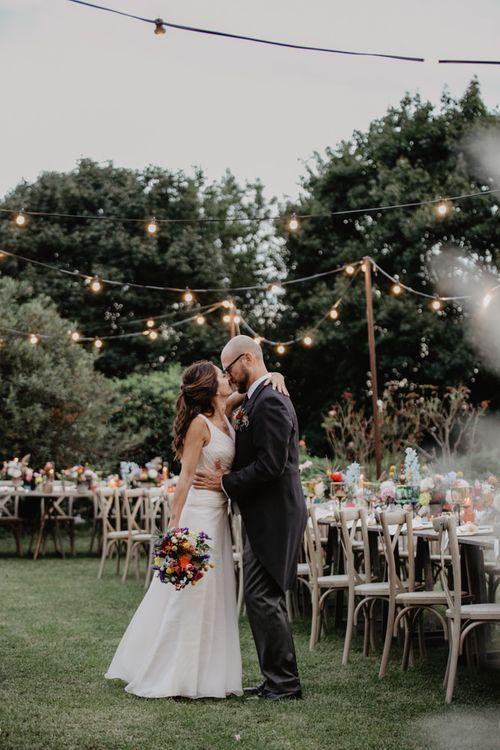 Festoon lighting at wedding with flower centrepieces