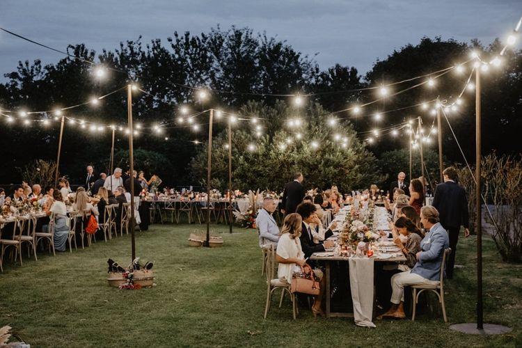 Guest enjoy wedding breakfast under festoon lighting