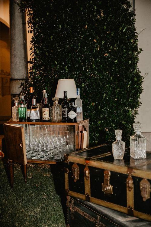 Whiskey station at wedding with bright flower centrepieces