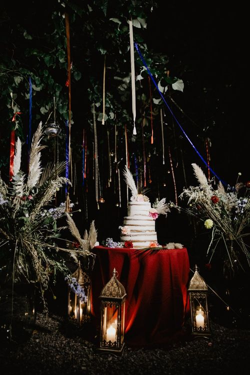Sami-naked wedding cake surrounded by tassels and pampas grass