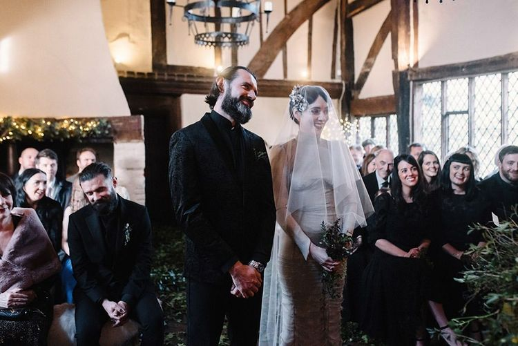 Bride and groom tie the knot at intimate gothic wedding ceremony with foliage decor