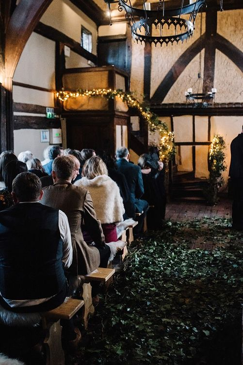 Gothic styled wedding ceremony with foliage decor and fairy lights