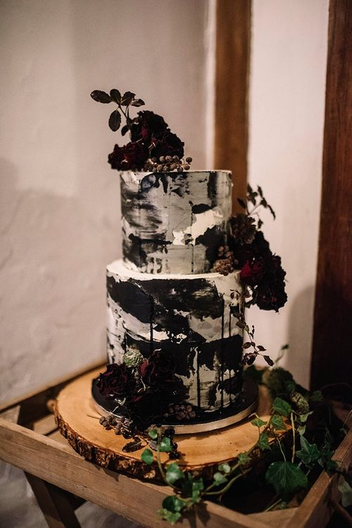 Cake at Gothic wedding with floral detailing on tree stump stand