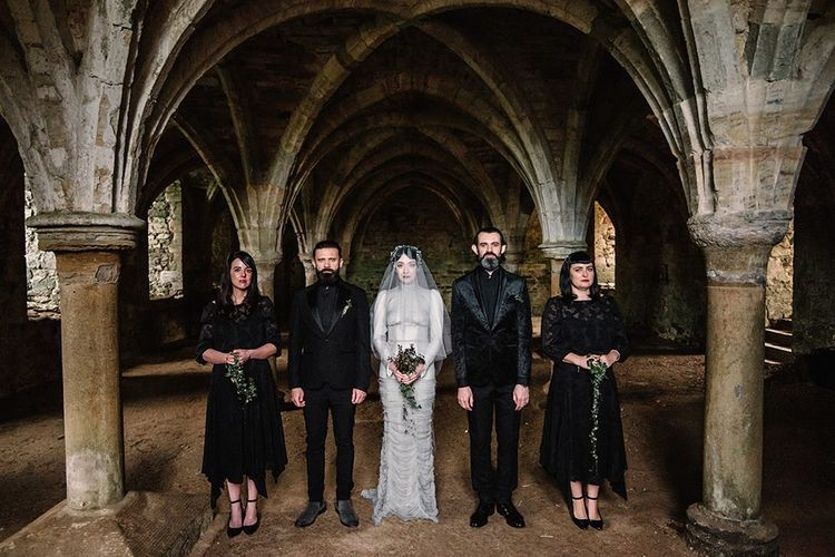 Bride wearing silver dress and bridesmaids in black dress with foliage bouquets for gothic wedding