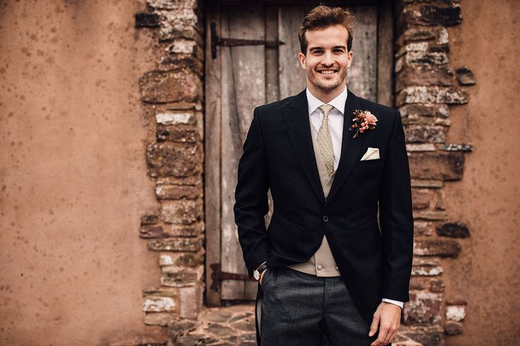 Groom in wedding suit with tails at Dewsall Court wedding