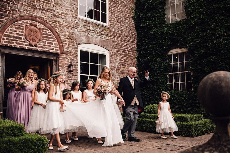 Bride with bridesmaids makes her way to church ceremony at Dewsall Court
