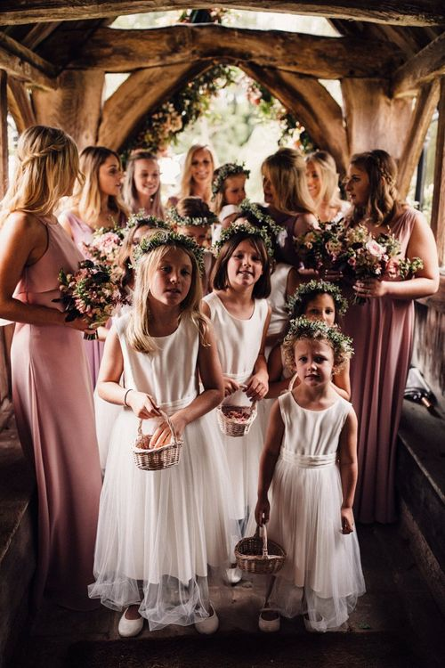 Bridesmaids and flower girls wait to enter church ceremony