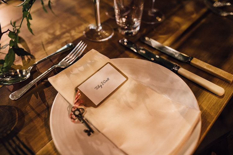 Wedding place setting with key and pink flowers