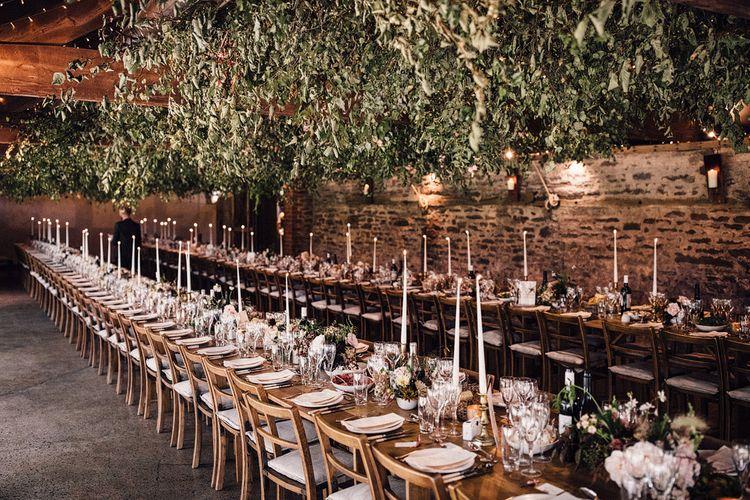Rustic wedding breakfast decor with hanging foliage