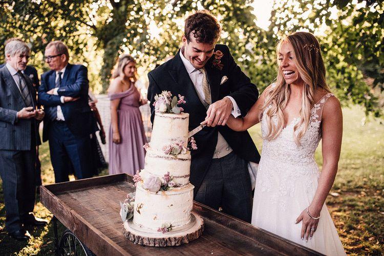 Bride and groom cut rustic wedding cake on tree slice cake stand