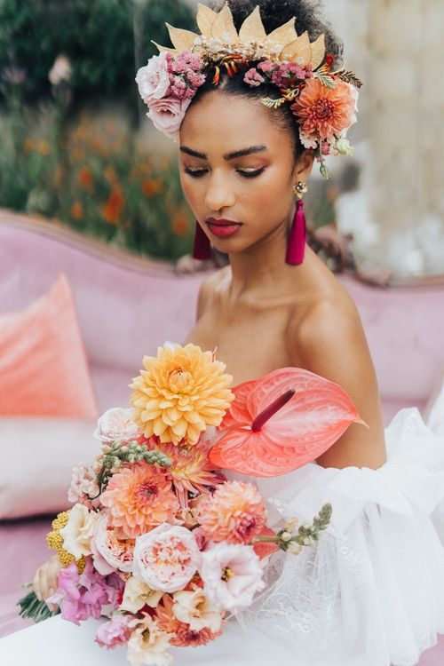Bride holding a blush pink, peach and coral wedding bouquet with dahlias and anthuriums  at Chiddingstone Castle