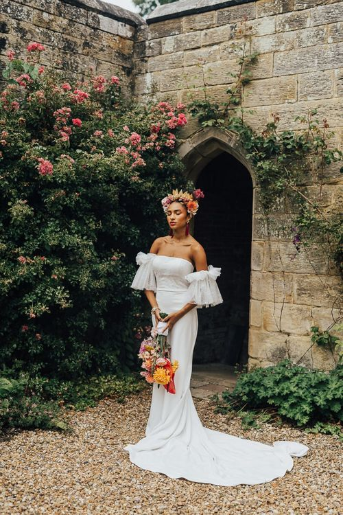Beautiful bride in strapless wedding dress with tulle sleeves in flower crown