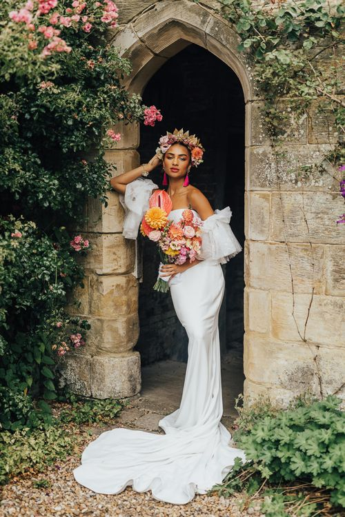 Black bride in fitted wedding dress holding a blush bridal bouquet at Chiddingstone Castle