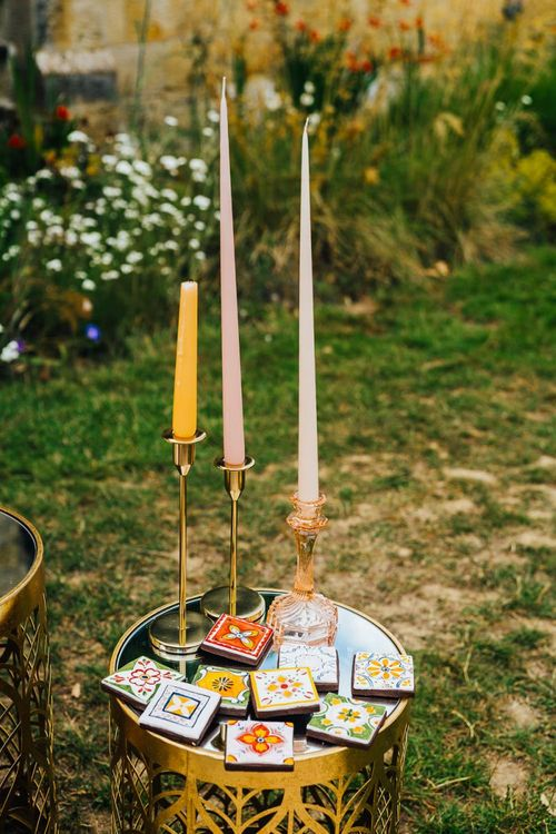 Gold candlesticks, coloured candles and tiles decor
