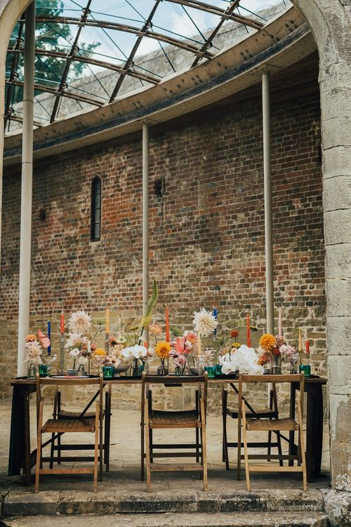 Outdoor table decor at Chiddingstone Castle with colourful flowers and candles