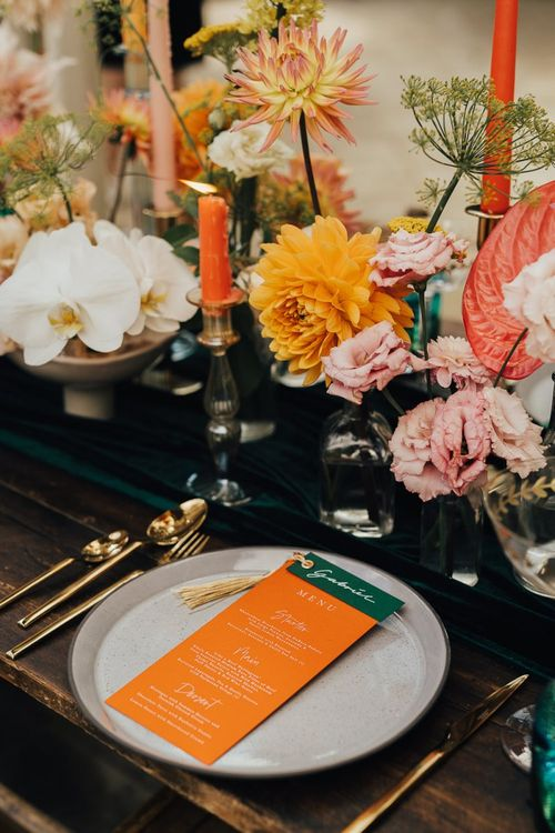 Place setting with gold cutlery and colourful menu card