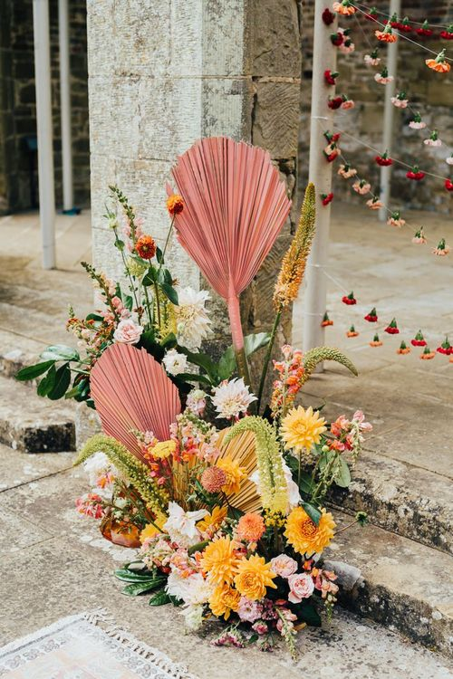 Colourful flower arrangement with pink spray painted palm leaf