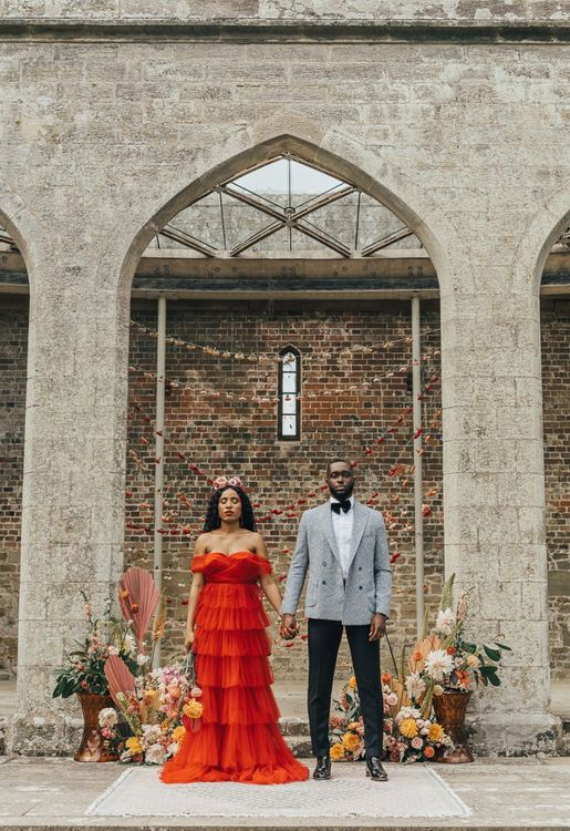 Stylish bride and groom in red dress and grey blazer at Chiddingstone Castle