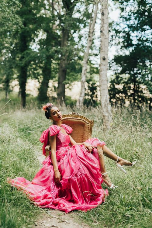 bride in pink Emma Beaumont wedding dress sitting on a chair in the woods