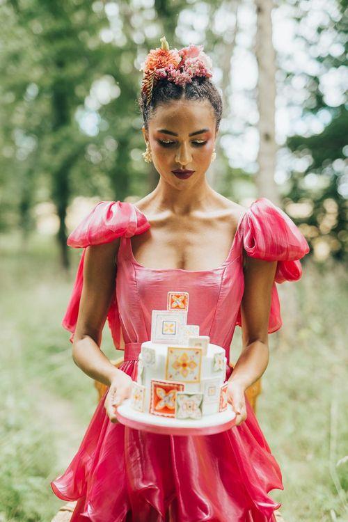 bride in pink wedding dress holding a wedding cake
