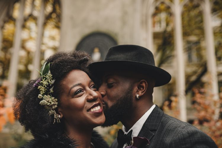 Stylish groom in hat kissing his bride with flower in her hair