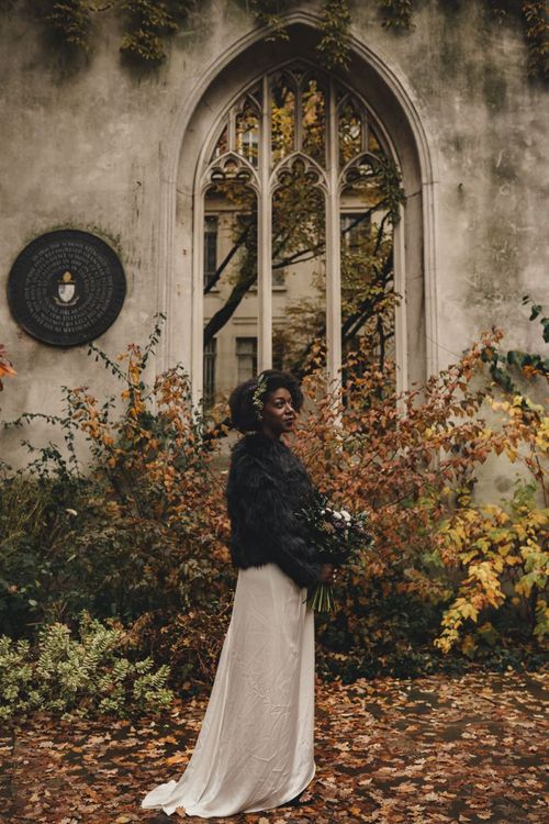Black bride in satin wedding dress and black faux fur coverup