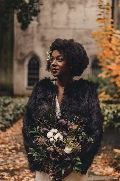 Black bride in faux fur cover up holding a deep purple calla lily wedding bouquet