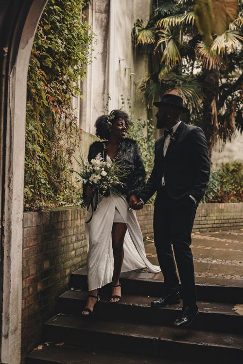 Stylish bride and groom walking through the St Dunstan in the East church gardens