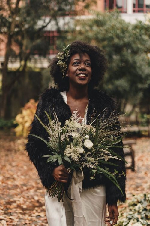 Black bride in faux fur coverup holding a green and white wedding bouquet  tied with ribbon