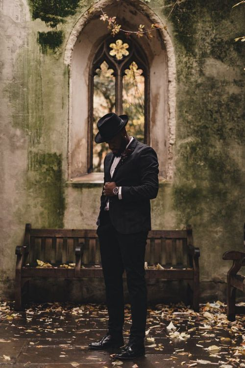 Stylish groom in tuxedo and hat at St Dunstan in the East