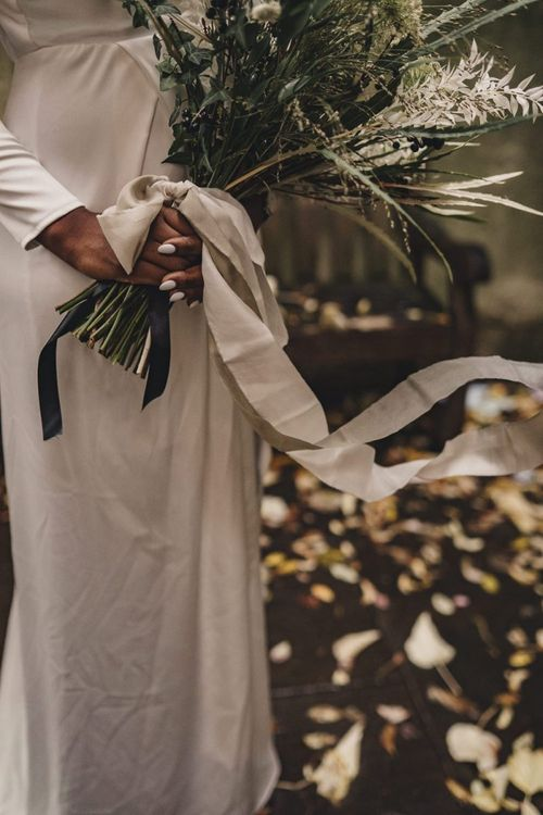 Black bride with white nail polish holding wedding bouquet tied with ribbon