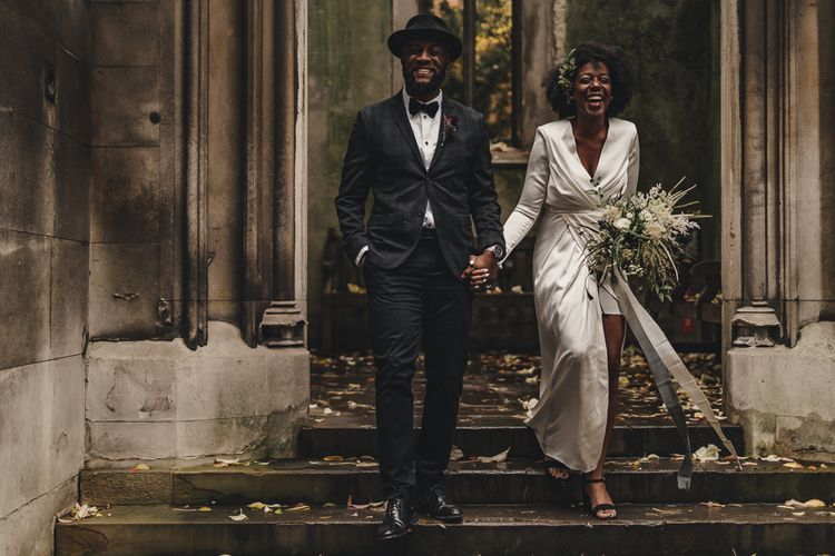 Black bride in high street wedding dress and groom in hat and bow tie for London wedding